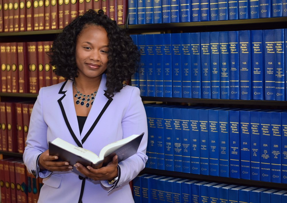A woman with dark curly hair, a lavender jacket and a confident expression stands in front of bookcases. She holds open a large hardcover book while looking at the viewer.